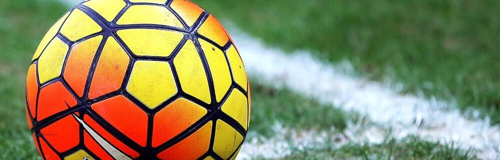 Die besten Online Sportwetten Close-up orange gelber Fussball auf Rasen