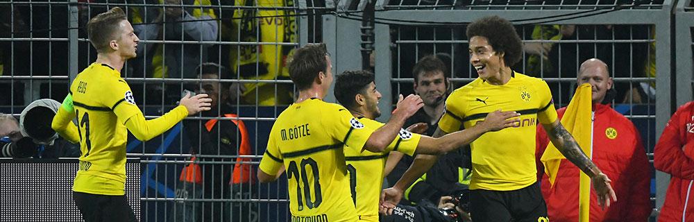 Die besten Online Sportwetten Close-up vier glückliche Fussballspieler vom BVB im Spiel im Hintergrund Publikum und Repräsentanten