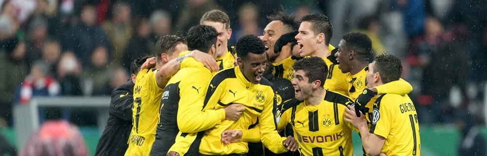 Die besten Online Sportwetten Close-up glückliche Spieler vom BVB umarmen sich und feiern auf dem Spielfeld