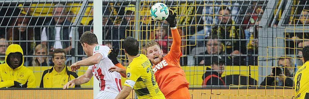 Die besten Online Sportwetten Close-up Fussballspiel zwei Spieler schauen Torhüter Hand am Ball