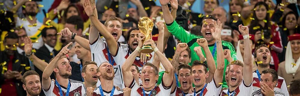 Die besten Online Sportwetten Close-up Fussballspieler Deutsche Nationalmannschaft feiern den Sieg mit Pokal und Konfetti