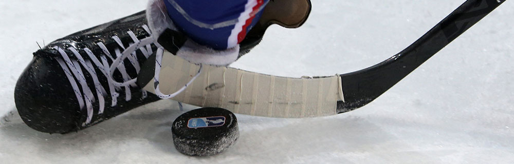 Die besten Online Sportwetten Close-up Eishockeyspieler auf Eis EIhockeyschuh Puk Schläger