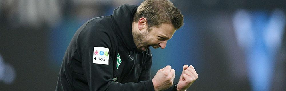 Die besten Online Sportwetten Close-up Fussballtrainer Kohlfeldt Werder Bremen auf Spielfeld Siegerpose