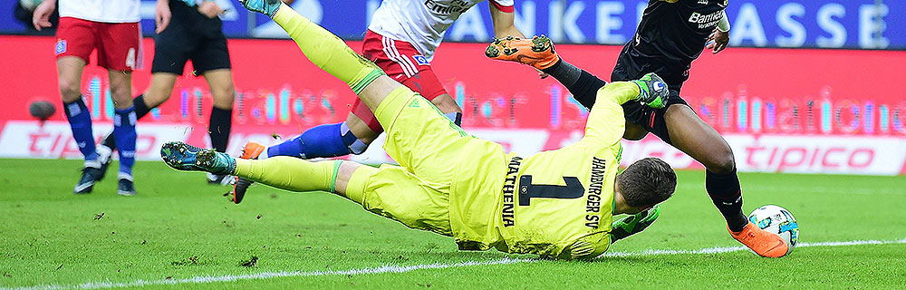 Die besten Online Sportwetten Close-up Fussballspiel zwei Spieler im Duell auf dem Spielfeld Torhüter Hamburger SV