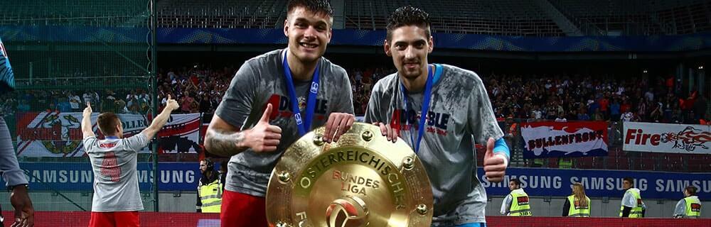 Die besten Online Sportwetten Close-up zwei Spieler mit Pokal auf dem Spielfeld Bundesliga