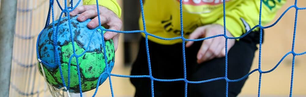 Die besten Online Sportwetten Close-up Handballspiel Tor Torhüter Hand mit Handball