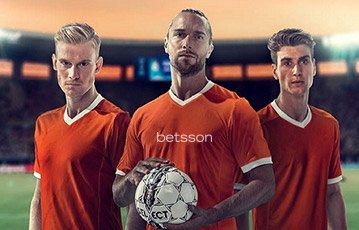 Die besten Online Sportwetten Close-up drei Fussballspieler auf dem Spielfeld Ball in Hand betsson