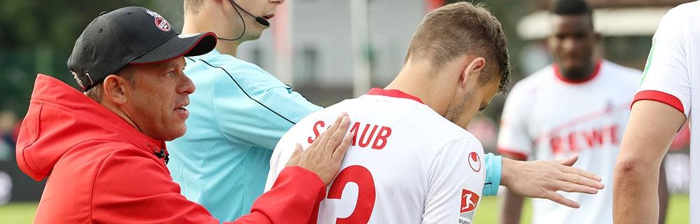 Die besten Online Sportwetten Close-up Fussballspiel Trainer und Fussballspieler auf dem Spielfeld bei Bundesliga