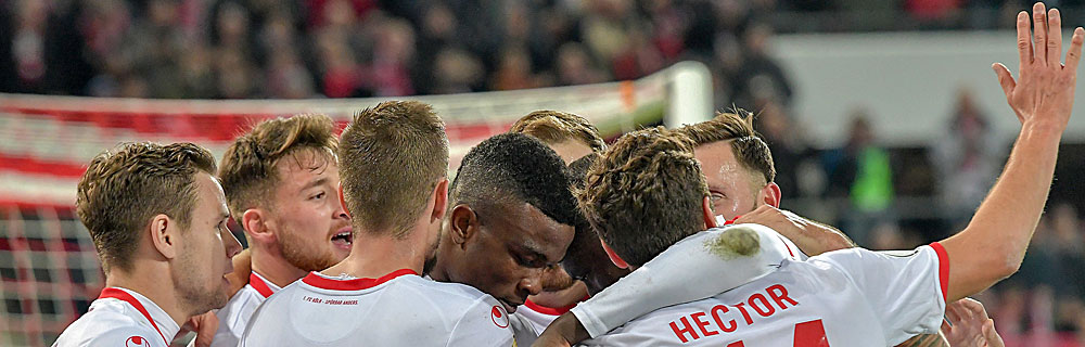 Die besten Online Sportwetten Close-up Fussballspieler auf dem Spielfeld Umarmung Bundesliga