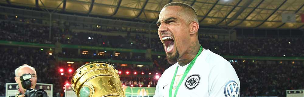 Die besten Online Sportwetten Close-up Fussballspieler auf dem Spielfeld mit Pokal in der Hand