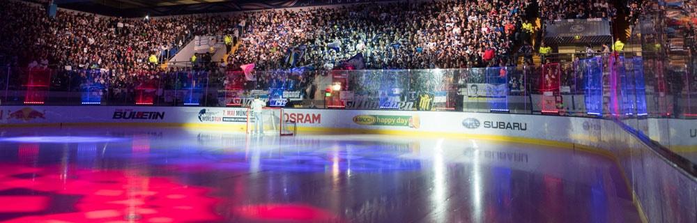 Die besten Online Sportwetten Close-up leeres und pink blau beleuchtetes Eishockeyfeld Zuschauer Tribüne