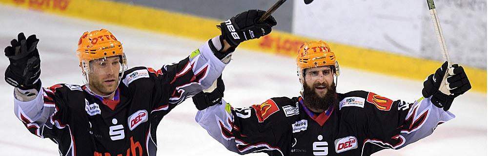 Die besten Online Sportwetten Close-up zwei Eishockeyspieler auf dem Eis Jubel Arme hoch