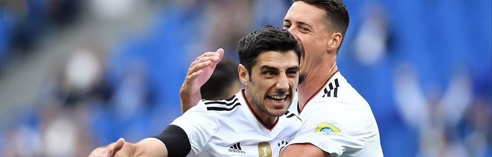 Die besten Online Sportwetten Close-up zwei Fussballspieler auf dem Spielfeld Umarmung