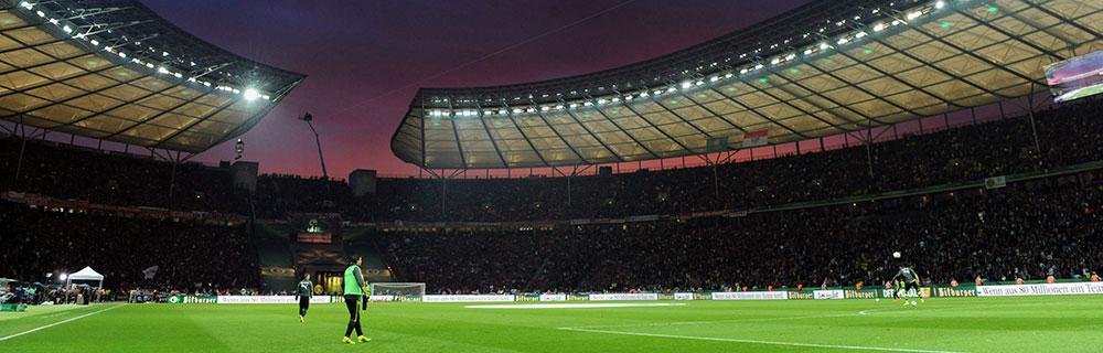 Die besten Online Sportwetten am Abend im Stadion beleuchtet Weitwinkel Fussballspieler auf Feld Zuschauer Fankurve