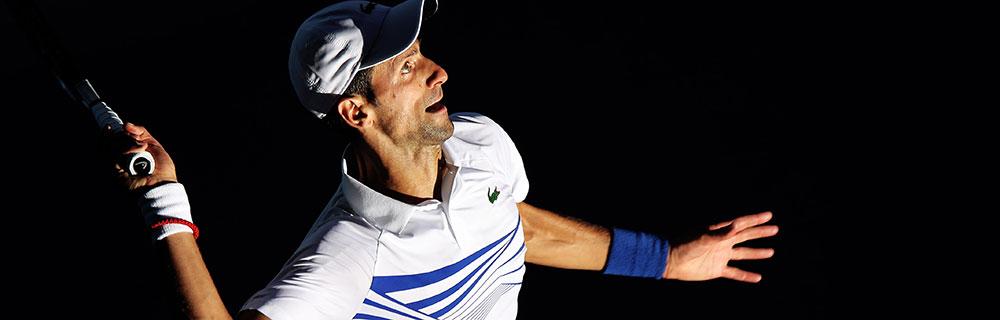 Die besten Online Sportwetten Close-up Tennisspieler Djokovic auf dem Spielfeld im Spiel fokussiert Ball