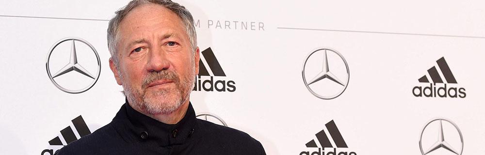 Die besten Online Sportwetten Close-up Mann mit schwarzem Oberteil vor Werbewand Adidas Mercedes Bundesliga