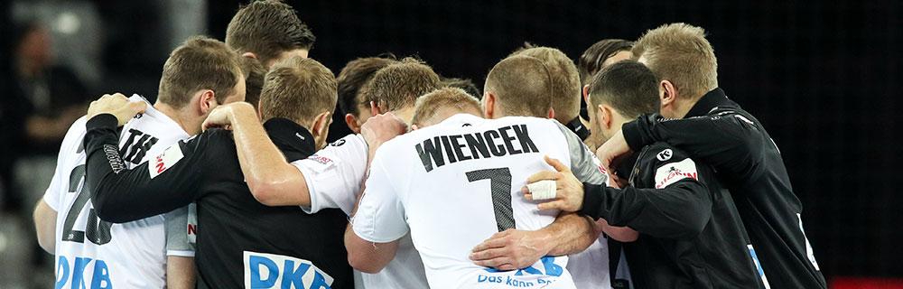 Die besten Online Sportwetten Close-up Handballspieler Kader auf dem Spielfeld Umarmung