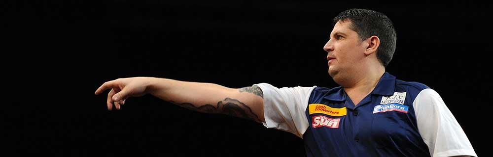 Die besten Online Sportwetten Close-up Dartspieler vor Dartscheibe Arm gestreckt nach Wurf