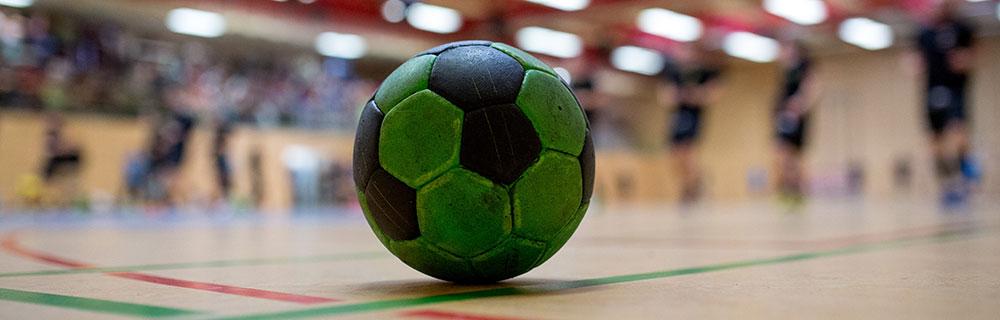 Die besten Online Sportwetten Close-up grün schwarzer Handball auf Spielfeld