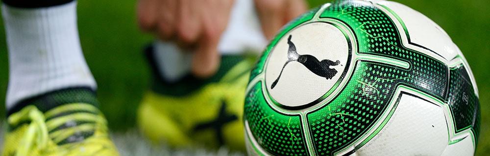 Die besten Sportwetten Online Close-up Rasen Fussballschuhe Fussball grün weiß schwarz mit Puma Logo