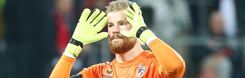 Die besten Online Sportwetten Close-up Fussball Torhüter auf Spielfeld Hände an Gesicht Handschuhe