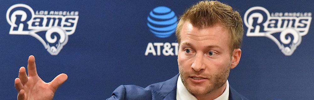 Die besten Online Sportwetten Close-up american football Spieler in Anzug vor Werbewand