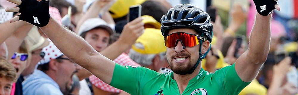 Die besten Online Sportwetten Close-up Radfahrer im Ziel Siegerpose Zuschauer im Hintergrund