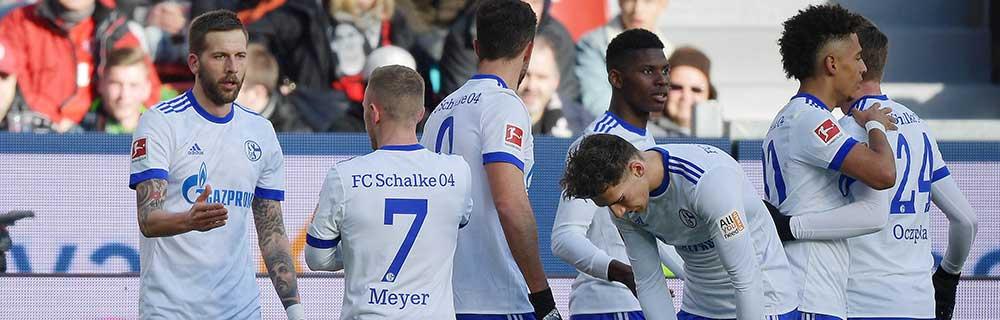 Die besten Online Sportwetten Close-up Fussballspieler auf dem Spielfeld Schalke Umarmung handshake