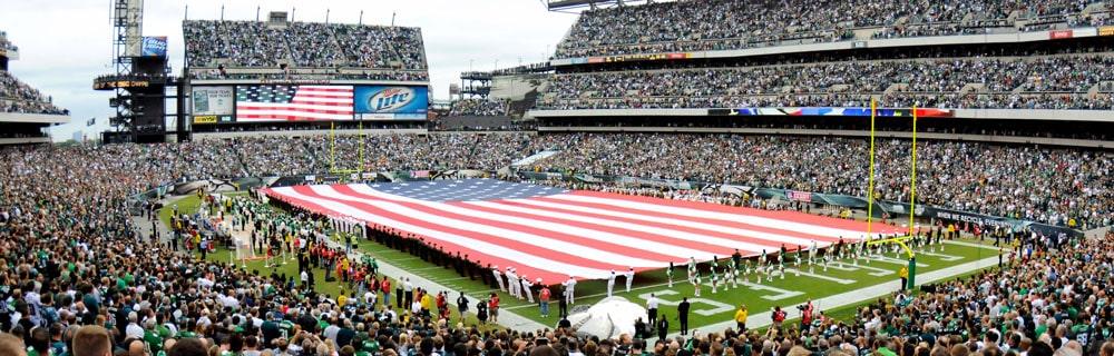 Die besten Online Sportwetten american football Vogelperspektive Spielfeld Spieler halten Amrika Flagge Zuschauer auf Tribüne