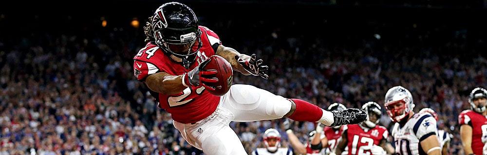 Die besten Online Sportwetten Close-up american football Spieler fängt Ball mit Hand im Sprung