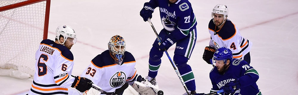 Die besten Online Sportwetten Close-up Eishockeyspieler auf dem Eis vor Tor