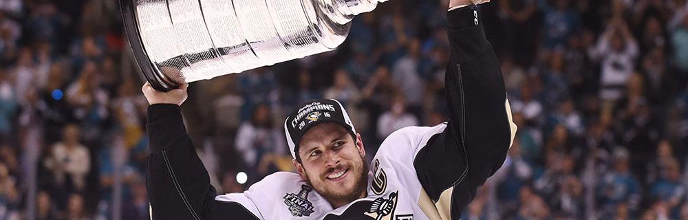Die besten Online Sportwetten Close-up Eishockeyspieler auf dem Eis hält Pokal hoch