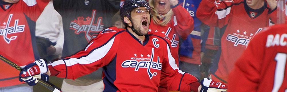 Die besten Online Sportwetten Close-up Eishockeyspieler Jubel auf dem Eis jubelnde Fans im Hintergrund