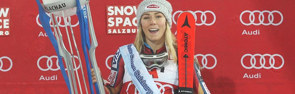 Die besten Online Sportwetten Close-up Skifahrerin Mikaela Shiffrin mit Ski und Pokal in der Hand vor Werbewand Audi