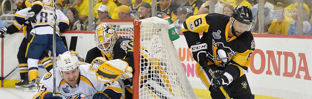 Die besten Online Sportwetten Close-up Eishockeyspieler auf dem Eis vor und hinter Tor