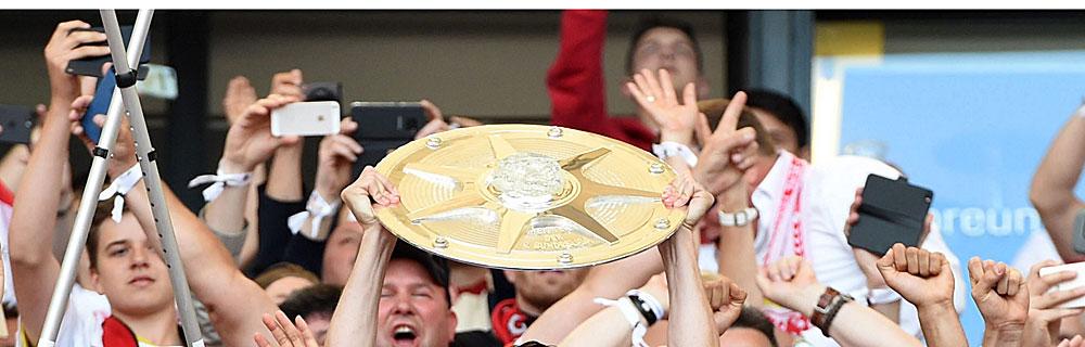 Die besten Online Sportwetten Close-up Fussballspieler und Fans Spieler halten Pokal in die Luft
