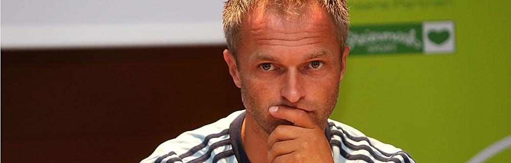 Die besten Online Sportwetten Close-up Gesicht Fussballtrainer Wück vor Werbewand