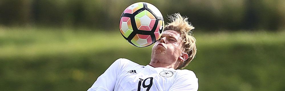 Die besten Online Sportwetten Close-up Fussballspieler auf dem Spielfeld Ball vor Gesicht