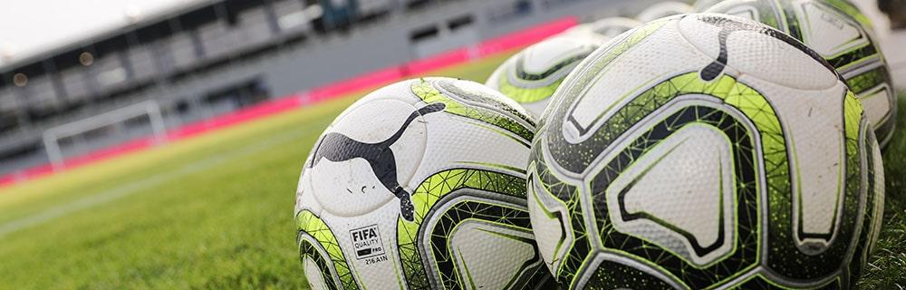 Die besten Online Sportwetten Close-up Fussbälle liegen auf Rasen Logo Puma