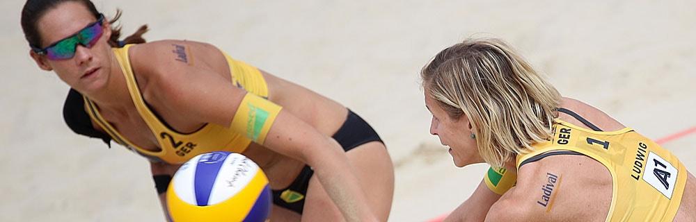 Die besten Sportwetten online Beachvolleyball close up zwei Spielerinnen auf dem Feld eine Sprung am Ball