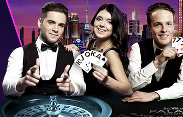 Die besten Online Casinos bei jackpotcity Close up zwei Groupiers in der Mitte eine Frau hält Spielekarten am Roulette skyline